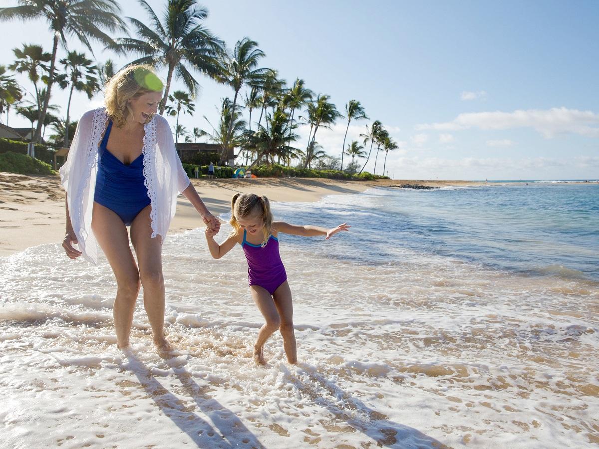 Ibu dan anak bercengkerama dan berdiri di dalam perairan pantai. Temukan destinasi dan pengalaman yang dapat Anda nikmati.