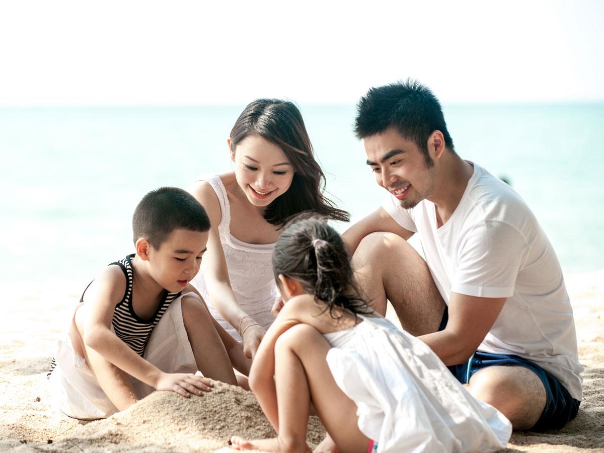 Family on beach building a sandcastle