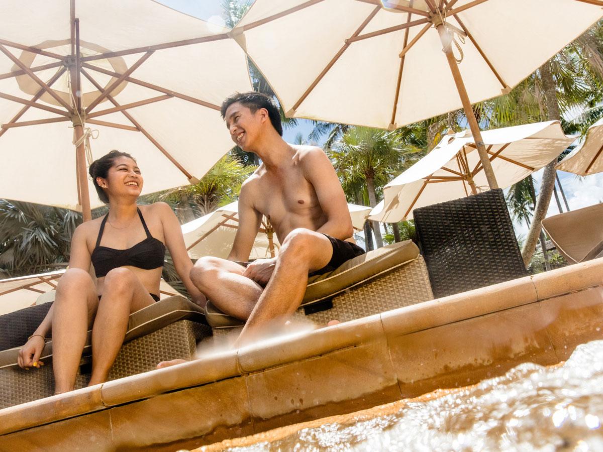 Pasangan di kolam renang. Liburan cara Anda. Temukan manfaat keanggotaan timeshare.