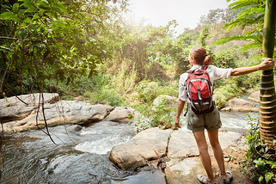 Woman exploring a rocky river on an Adventure Travel experience. Create your own thrilling adventures.