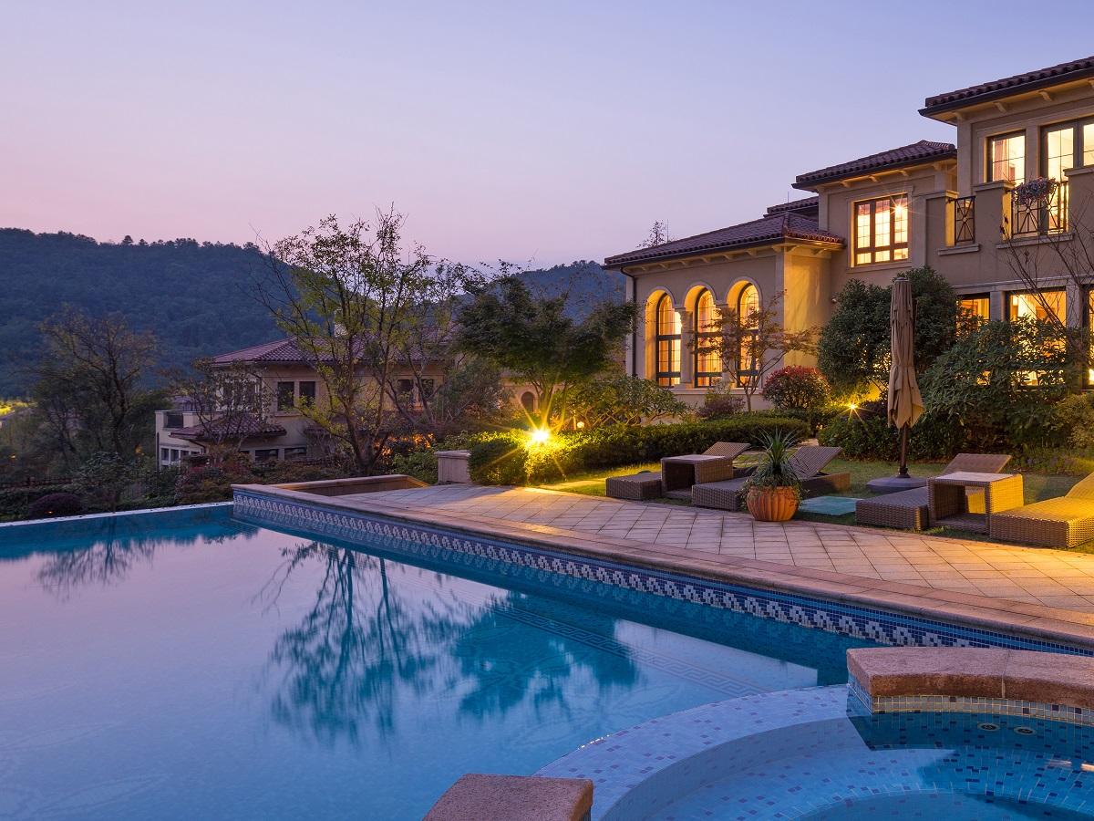 Foto rumah liburan apik dari kolam renang saat senja. Rumah liburan. Temukan tempat baru yang senyaman rumah sendiri.